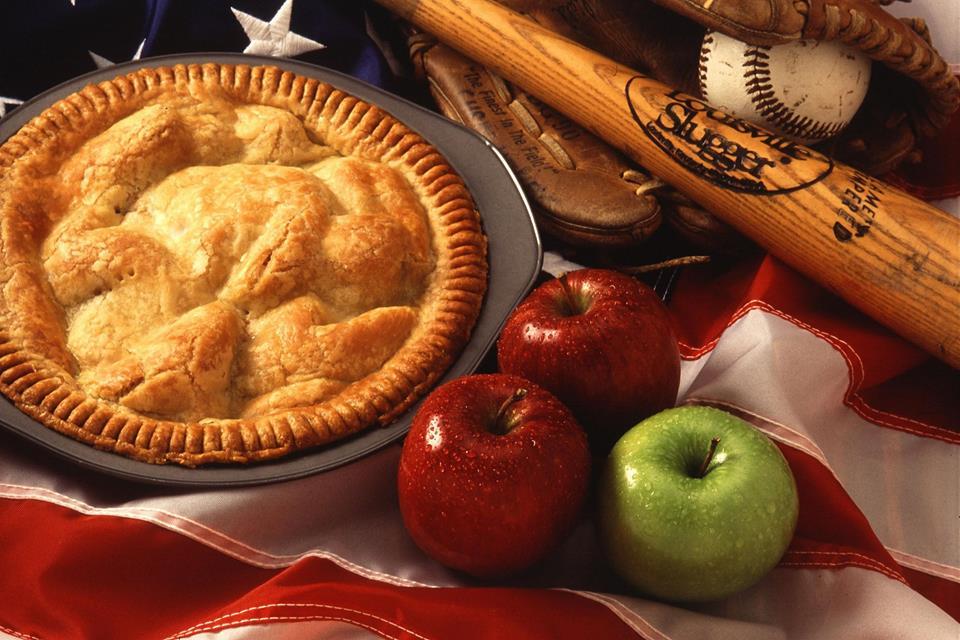Baseball equipment and an apple pie lying on an American flag